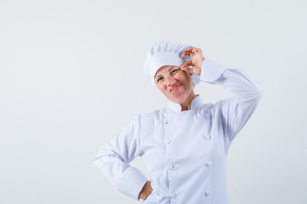 Woman chef pinching her eyelid in white uniform and looking weird