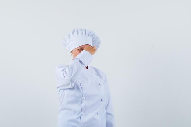 Chef donna pizzicandosi il naso in uniforme bianca e guardando turbato