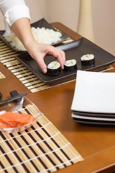 쟁반에 일본 스시 롤을 놓는 여성 요리사
