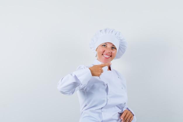 白い制服を着て脇を向いて幸せそうに見える女性シェフ