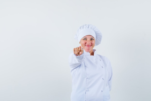 Женщина-повар показывает вперед в белой униформе и радуется