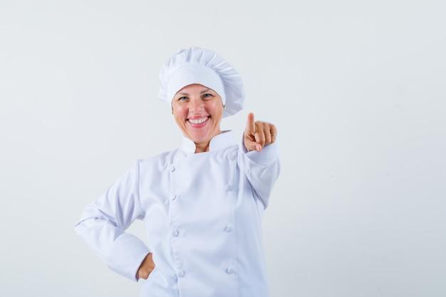 Женщина-повар показывает вперед в белой форме и выглядит весело