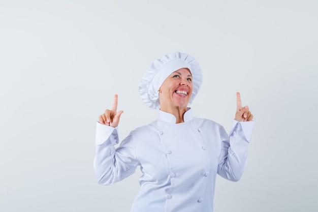 Женщина-повар показывает вверх в белой униформе и смотрит оптимистично