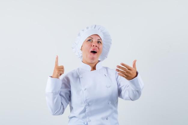 Chef donna in posa come scegliere qualcosa al menu in uniforme bianca