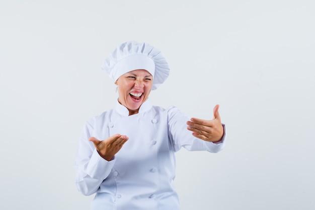 Женщина-шеф-повар позирует, как смеется, глядя на телефон в белой униформе и выглядит весело