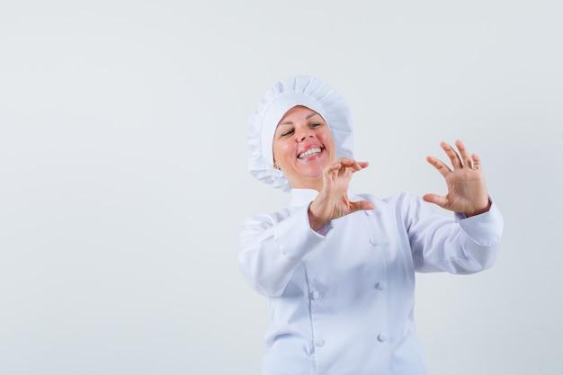 Chef donna in posa come scattare foto di qualcuno in uniforme bianca e guardando positivo.