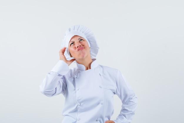 Chef donna in posa come parlare al telefono mentre pensa in uniforme bianca e guardando concentrato