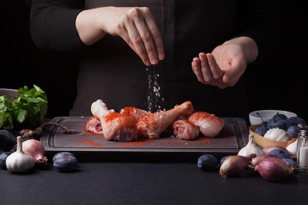 A woman chef prepares a chicken.