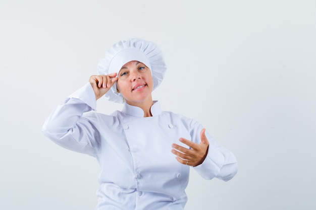 Woman chef pretending to do makeup in white uniform and looking delicate