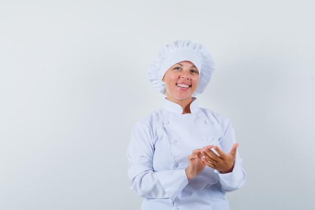 흰색 유니폼에 휴대 전화를 사용하는 척하고 행복을 찾는 여자 요리사