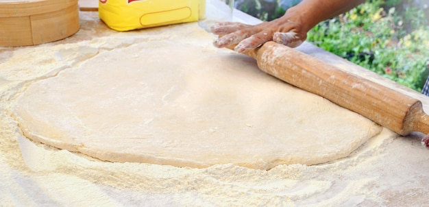 Женщина-повар раскатывает дрожжевое тесто скалкой на столе. скопируйте пространство. готовим на открытом воздухе. мастер-класс по приготовлению сладких пончиков.