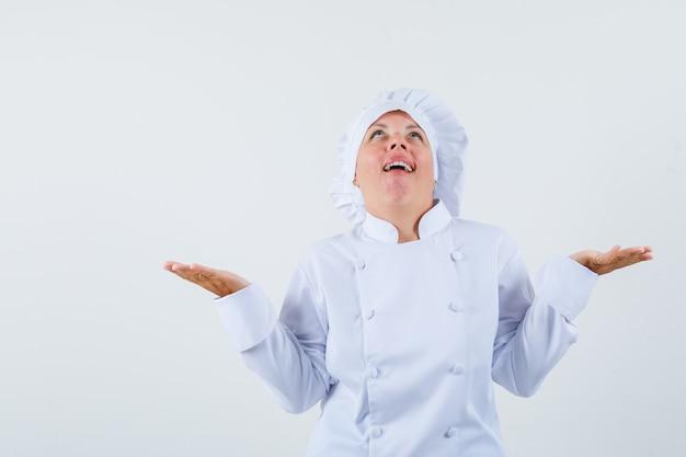 흰색 유니폼에 무기력 한 제스처를 보여주는 희망을 찾고 여자 요리사