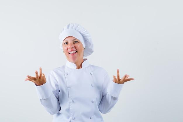 Женщина-повар демонстрирует беспомощный жест в белой форме и недоумевает