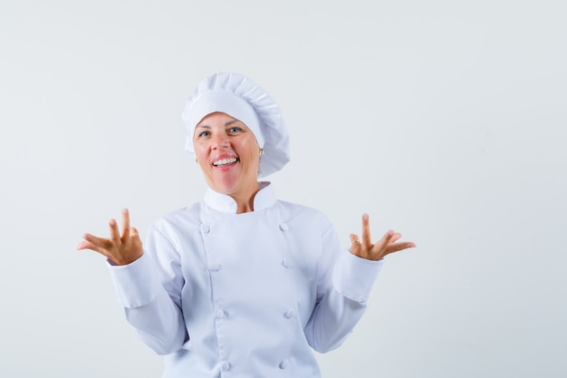 Woman chef showing helpless gesture in white uniform and looking puzzled