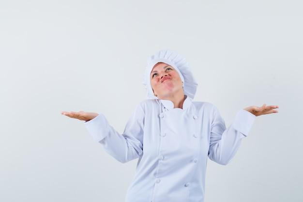 Chef donna che mostra gesto impotente in uniforme bianca.