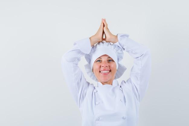 白い制服を着て頭上にナマステジェスチャーを示し、幸せそうに見える女性シェフ