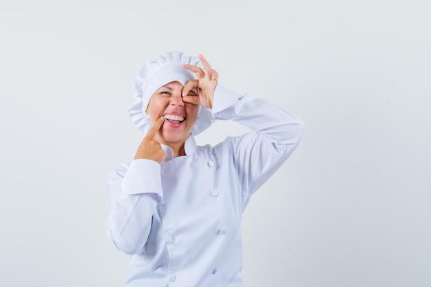 白い制服を着た目にokサインを示し、楽観的に見える女性シェフ。