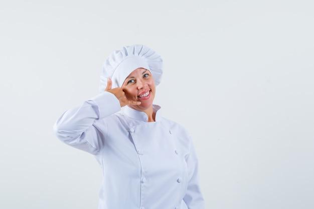 Chef donna che mostra il gesto della telefonata in uniforme bianca e sembra ottimista.