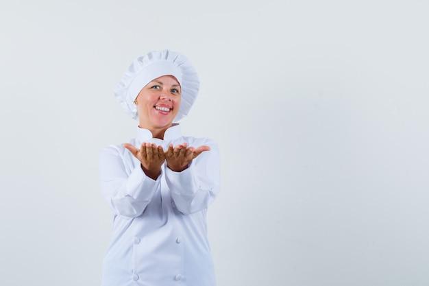 Женщина-повар показывает что-то кому-то в белой форме и выглядит довольной
