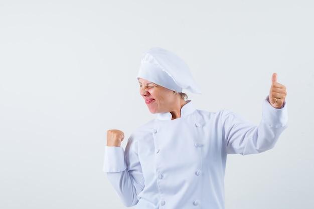 Chef donna che mostra il pollice in su mentre mostra il gesto del vincitore in uniforme bianca e sembra allegro