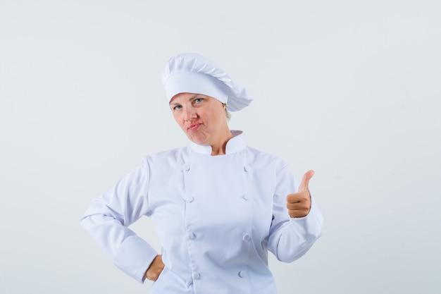 Chef donna che mostra il pollice in su in uniforme bianca e sembra soddisfatto
