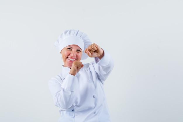 흰색 유니폼과 유쾌한 찾고 승자 제스처를 보여주는 여자 요리사