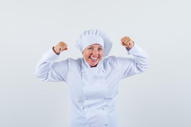 Женщина-повар показывает жест победителя в белой форме и выглядит радостным.