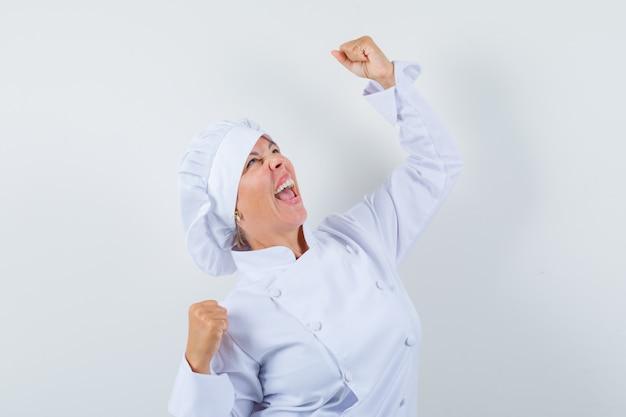 白い制服を着て勝者のジェスチャーを示し、幸運に見える女性シェフ。