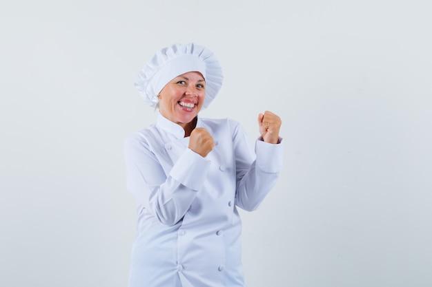 Chef donna che mostra il gesto del vincitore in uniforme bianca e sembra allegro