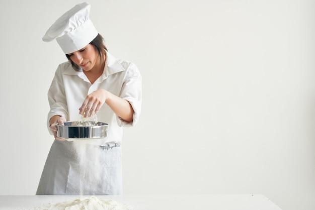 テーブルベーカリー料理ペストリーで小麦粉をふるいにかける女性シェフ