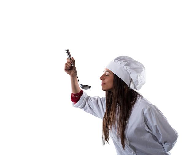 국자에서 향기를 냄새 맡는 여자 요리사