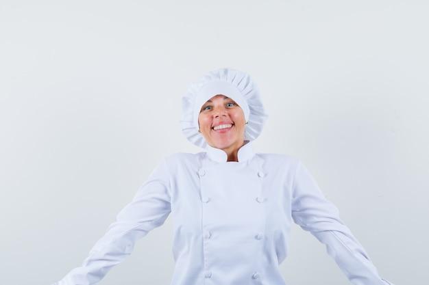 白い制服を着て腕を広げて幸せそうに見える女性シェフ。