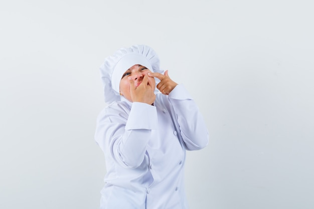 白い制服を着て頬ににきびを絞る女性シェフ
