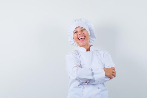 白い制服を着て腕を組んで立って幸せそうに見える女性シェフ。
