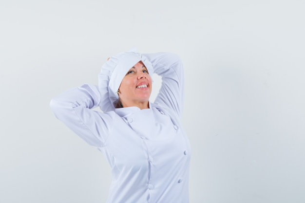 Woman chef stretching upper body in white uniform and looking relaxed