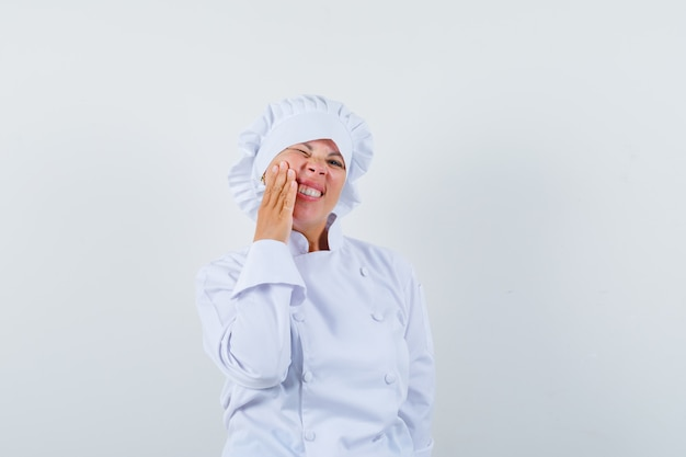 Woman chef in white uniform having toothache and looking uncomfortable