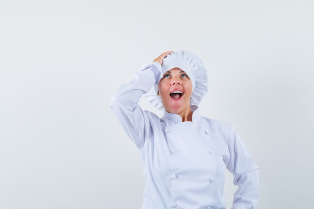 Woman chef in white uniform holding hand on head and looking amazed