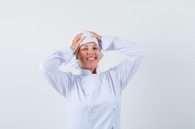 Chef donna in uniforme bianca tenendo le mani sulla testa e guardando ottimista