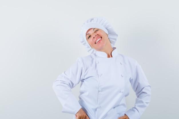 Chef donna in uniforme bianca tenendo le mani sulla vita e guardando fiducioso