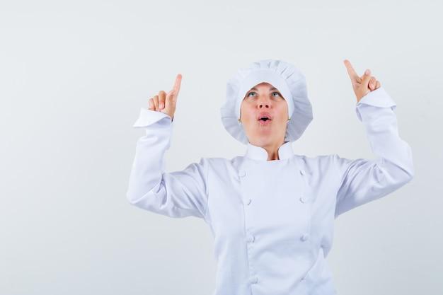 Chef donna in uniforme bianca rivolta verso l'alto e guardando speranzoso