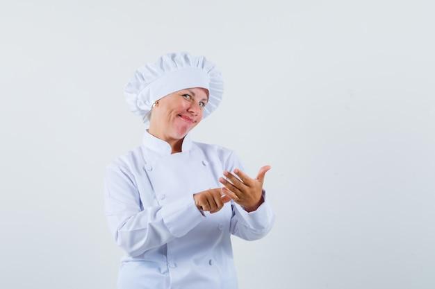 Chef donna in uniforme bianca in posa come leggere il nome dei pasti ordinati e sembra soddisfatta
