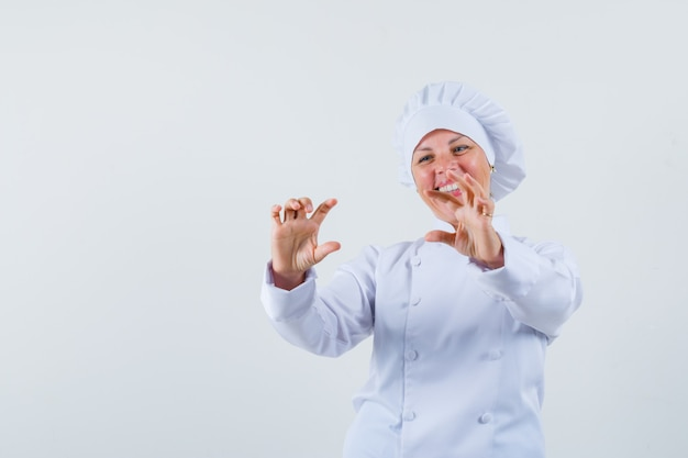 Chef donna in uniforme bianca in posa come scattare foto di qualcuno e sembra soddisfatto