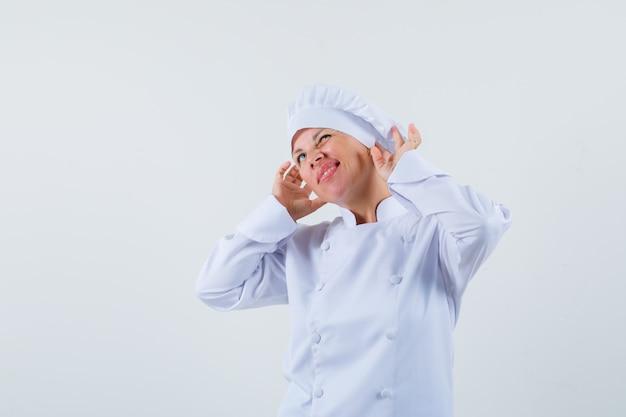 Chef donna in uniforme bianca in posa come indossare gli auricolari e guardando divertito