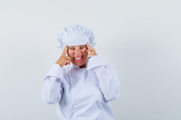 Chef donna in uniforme bianca tirando la pelle sulle tempie e guardando stanco
