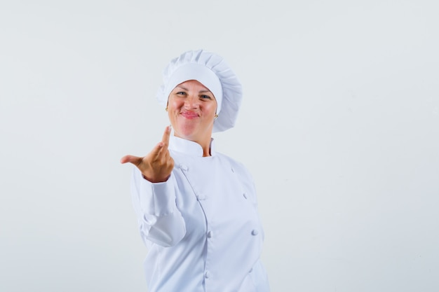 Woman chef in white uniform raising hand in questioning manner and looking energetic