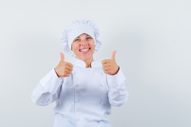 Woman chef in white uniform showing double thumbs up and looking cheerful