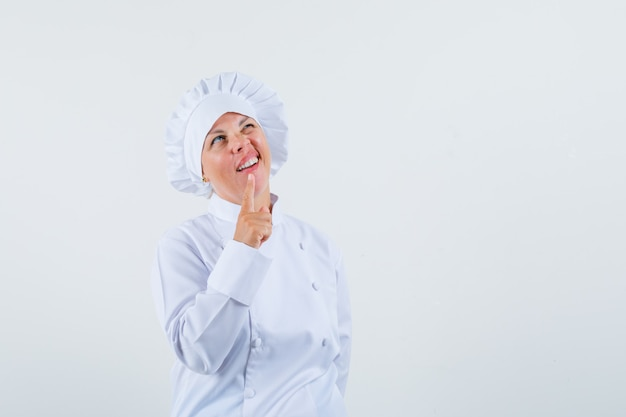 Woman chef in white uniform showing one minute gesture and looking pensive space for text