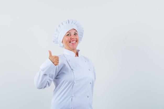 Chef donna in uniforme bianca che mostra il pollice in alto e sembra felice