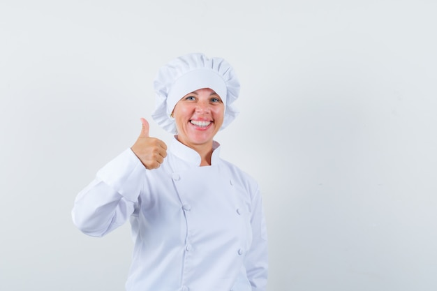 Woman chef in white uniform showing thumb up and looking merry