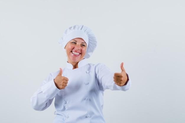 Chef donna in uniforme bianca che mostra pollice in alto e sembra ottimista